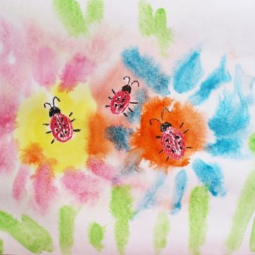 Draw little ladybugs on a flower meadow with your kid