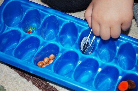 Предложите ребенку поиграть с формой для льда и пинцетом