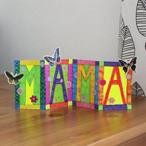 нарисованная поздравительная открытка для мамы с бабочками стоит на столе