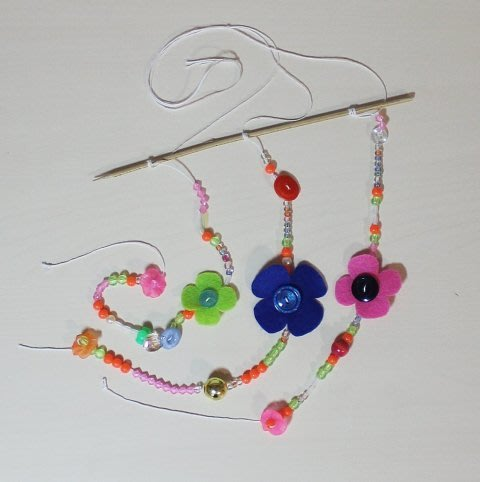 Make a pretty pendant with beads and buttons!