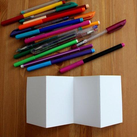 белый лист согнутый гармошкой и карандаши с фломастерами и маркерами на столе
