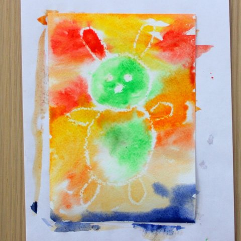 акварельные краски необычно выглядят на мокром листе бумаги с рисунком выполненном восковым мелком